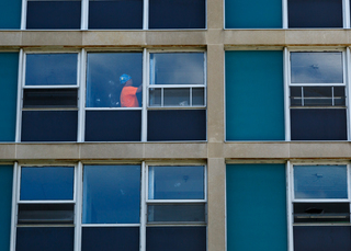 A construction worker in DellPlain Hall is seen through a window, as dorm room upgrades continue before the fall semester begins. Photo taken July 18, 2017